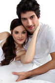 Young couple hugging in bed — Stock Photo