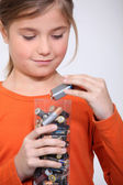 Young girl putting used batteries in a plastic container — Stock Photo