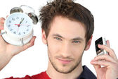 Man stood alarm clock and mobile — Stock Photo