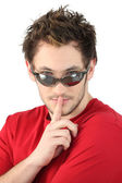 Man wearing sunglasses, shushing — Stock Photo