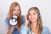 Young girl oblivious to her friend yelling into a megaphone — Stock Photo