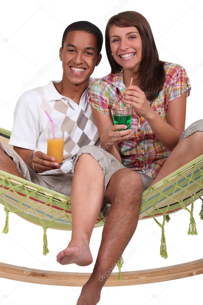 Couple enjoying tropical cocktails whilst sat on hammock — Stock Photo #14560587