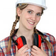 Young craftswoman wearing earphones — Stock Photo