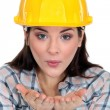 Tradeswoman blowing kisses - Stock Photo