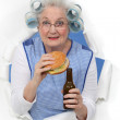 Old woman with beer and a burger — Stock Photo