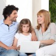 Parents and daughter using a laptop — Stock Photo