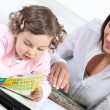 Stock Photo: Mum and daughter reading together