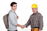 Construction worker shaking hands with a college student — Stock Photo