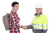 Young apprentice with backpack shaking hands with senior foreman — Stock Photo