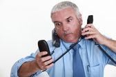 Businessman overwhelmed with phone calls — Stock Photo
