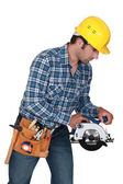 A manual worker with a circular saw. — Stock Photo