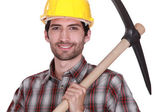 A construction worker with a pickaxe. — Stock Photo