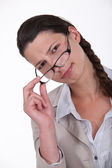 Woman peering over her glasses — Stock Photo