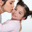 Woman kissing cute little girl — Stock Photo