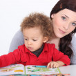 Stock Photo: Mother and son reading book together