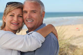 Senior couple embracing on the beach — Stock Photo