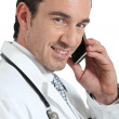 Doctor on phone smiling — Stock Photo