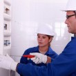 Fully-fledged electrician and female apprentice — Stock Photo #14637295