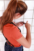 Woman using a screwdriver for putting an outlet — Stock Photo