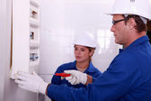 Fully-fledged electrician and female apprentice — Stock Photo