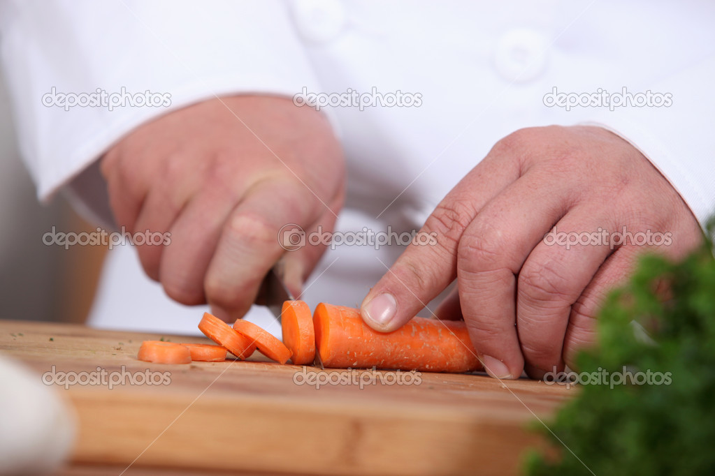 Closeup of a cook cutting carrots — Stock Photo #14634229