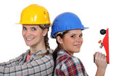 Women in hard hats with a carpenter — Stock Photo