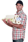 Man carrying rolls of wall-paper — Stok fotoğraf