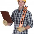Stock Photo: Worker holding spirit level and clip-board
