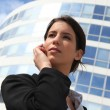 Woman in front of glass building - Stock Photo