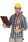 Worker holding spirit level and clip-board — Stock Photo