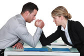 Arm wrestling between male and female colleagues — Stock Photo