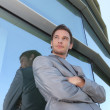 Businessman standing next to window — Stock Photo #14660599