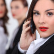 Business woman making call colleagues in background — Stock Photo