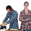 A man using a circular saw and a woman - Stock Photo