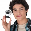 Young man holding a webcam — Stock Photo