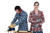 A man using a circular saw and a woman — Stock Photo