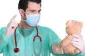 Man dressed as a surgeon quarrelling with teddy bear — Stock Photo