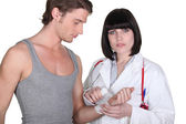 Doctor wrapping gauze around a patient — Stock Photo