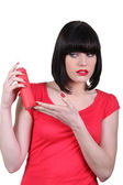 Woman in red looking warily at an aerosol — Stock Photo