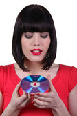 Dark -haired woman holding compact disc in hands — Stock Photo