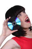 A woman sticking a cd near her ear — Stock Photo