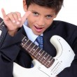 A little boy playing guitar and doing the horn sign - Stock Photo