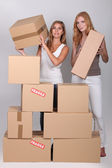 Young women stacking boxes — Stock Photo