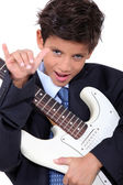A little boy playing guitar and doing the horn sign — Stock Photo