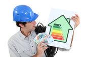 Artesano sosteniendo una etiqueta de consumo de energía — Foto de Stock