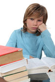 A bored child reading a book — Stockfoto