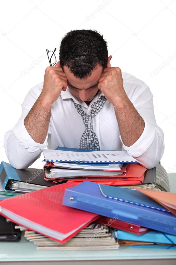 Depressed businessman surrounded with paperwork — Stock Photo #14675157
