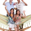 Young friends around a hammock — Stock Photo