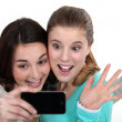 Two girls posing with camera phone — Stock Photo #14684793