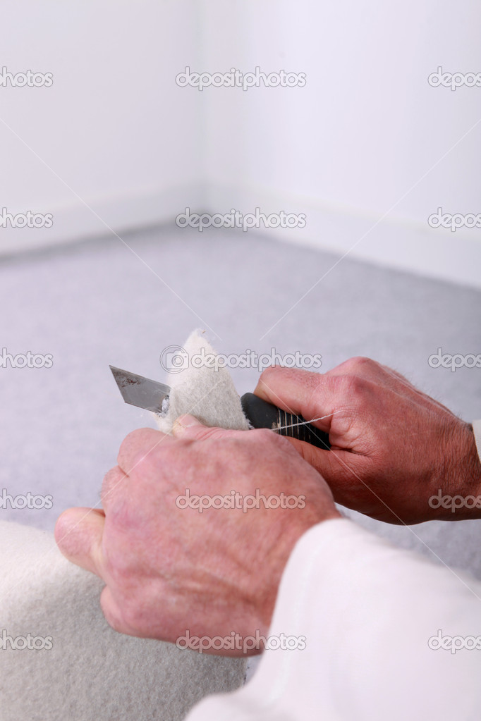 Closeup of a man cutting material with a utility knife  Stock Photo #14686807